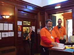 The happy, smiling men and women in orange get ready to welcome visitors.