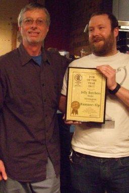 Former Branch Chairman John Cryne (left) presents Joe at The Jolly Butchers with their Award.