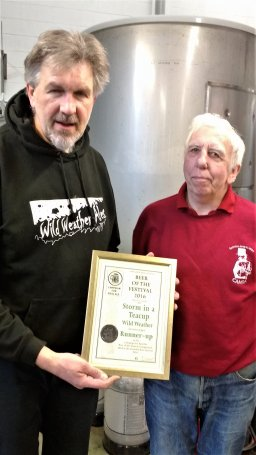 Bill Bendall presents a beer of the festival runner-up certificate to Mike Tempest the owner of Wild Weather.