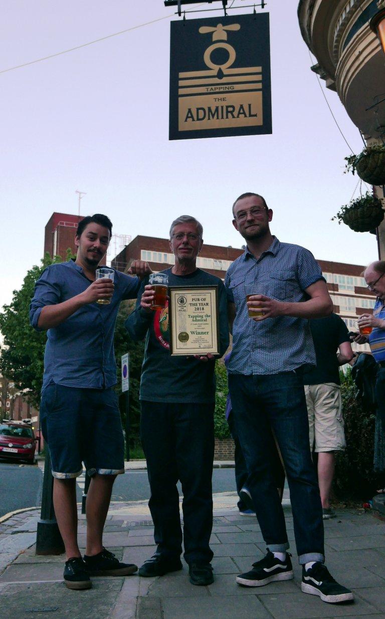 Phil Stewart (L) and Josh Freeborn (R) accept their 2018 North London Pub of the Year Award from John Cryne