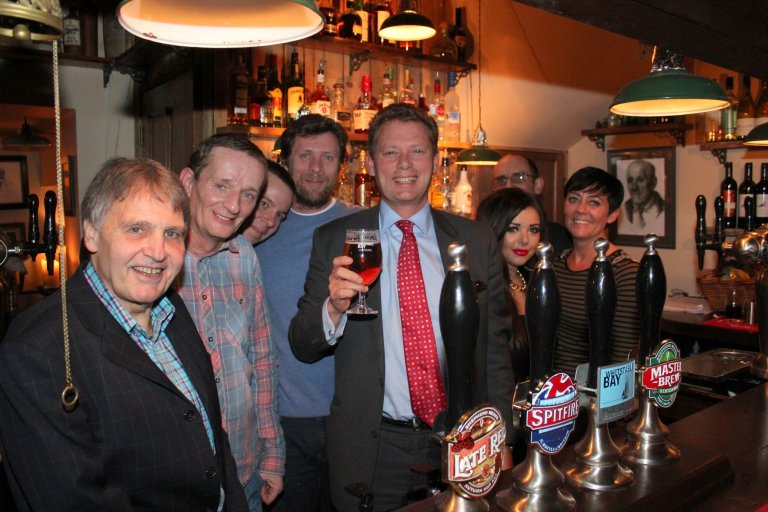 Former licensee Dixie Dean (left), new licensee Euan Johnstone (in blue) and Shepherd Neame chief executive Jonathan Neame with the bar team.