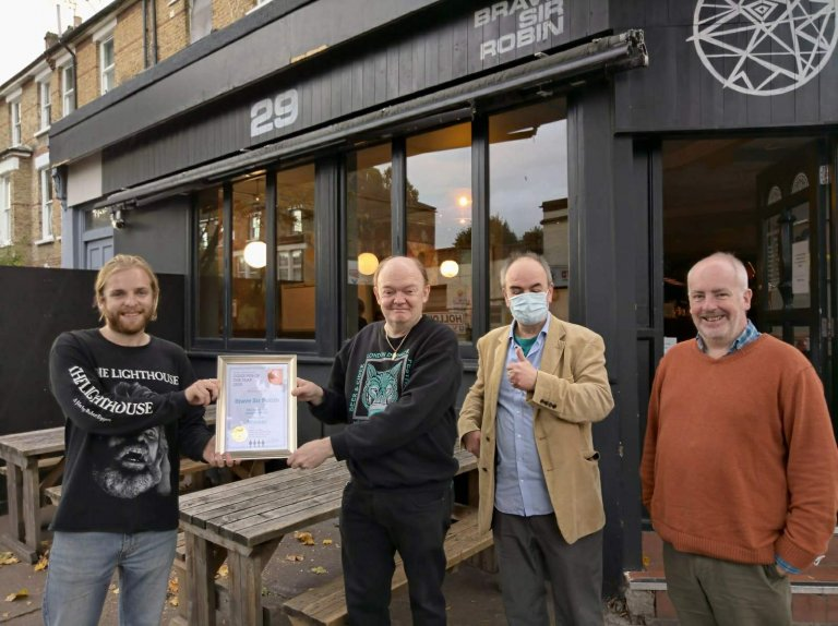 Archie Oxenbould (left) accepts the Award from Branch Chairman Colin Coyne with masked and unmasked CAMRA members on hand.