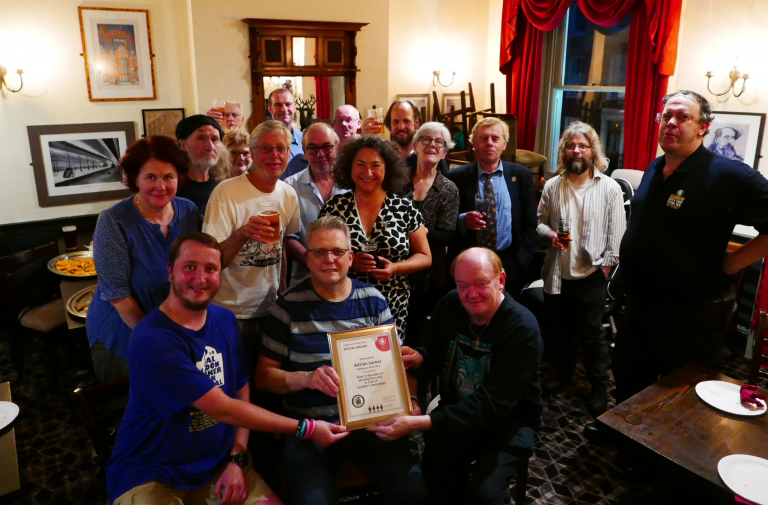 Adrian Larner (centre front) accepts his Award from CAMRA members.
