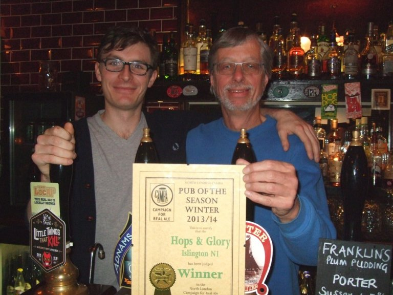 Durham Atkinson (left) of Hops & Glory receives the CAMRA North London 2013/2014 Winter Pub of the Season Award from CAMRA's John Cryne.