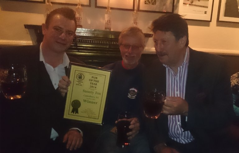 Jonathan Tingle (left) and Stuart Gale (right and father of licensee Nicole Gale) accept the 2014 North London Pub of the Year Award from John Cryne.