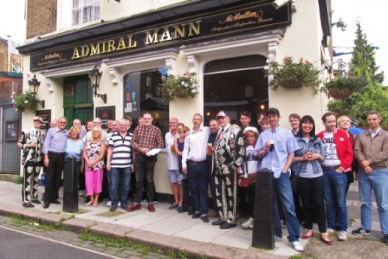 Local residents gather outside the Admiral Mann to protest at its sale and impending closure.