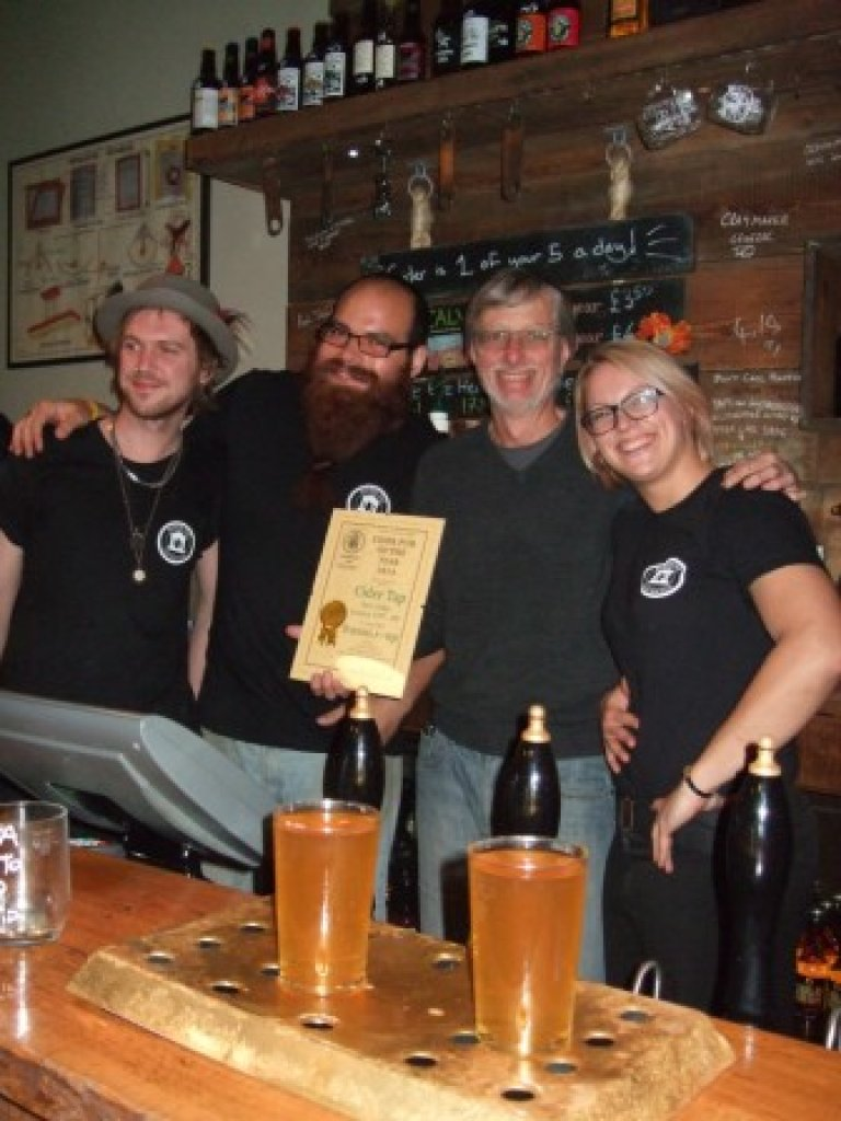 Dave Kennedy, Hector Estevez and Saara Mattinen looking happy at receiving CAMRA North London's 2014 Cider Pub of the Year Runner-up Award from John Cryne