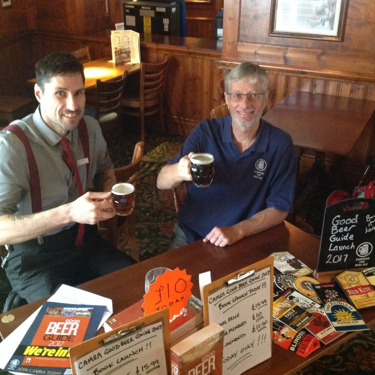 Manager Thomas Vercetti (left) toasts the inclusion of J J Moons, Kingsbury in the 2017 Good Beer Guide with Branch Chairman, John Cryne.