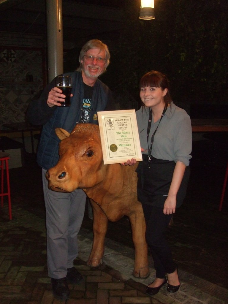 Genevieve Gardiner (right) accepts the Award from John Cryne while the cow looks on!